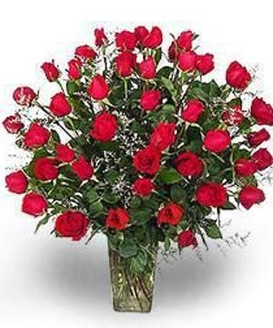 Two dozen red roses in a clear glass vase.