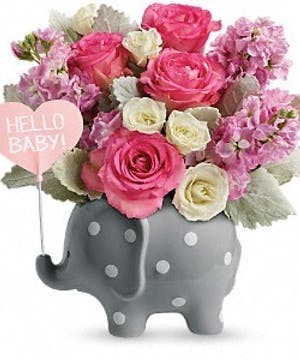 White and pink roses in a polka dot elephant container.