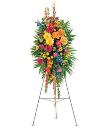 Sympathy spray of bright flowers and greenery displayed on an easel.
