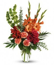 Sympathy bouquet of red roses, alstroemeria, gladioli and more in a Ming urn.