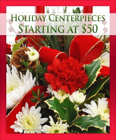 Holiday centerpiece of assorted flowers, candles, trim and greenery.