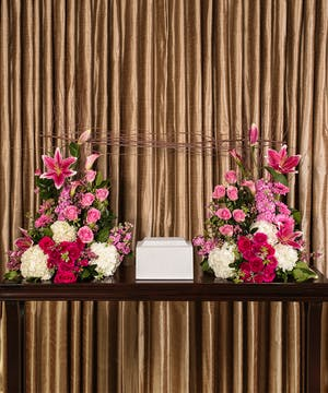 Collection of bright pink and white flowers to surround an urn.