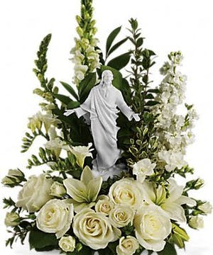 Sympathy bouquet of all-white flowers and a porcelain Jesus statue.