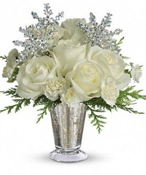 All-white arrangement of flowers and greenery with sparkling snowflake accents in a mercury glass vase