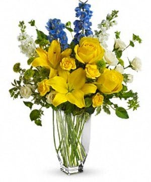Yellow and blue flowers in a tall glass vase.