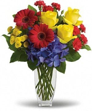 Blue hydrangea, yellow roses, red gerberas and miniature carnations, and yellow button spray chrysanthemums in a Jewel Vase
