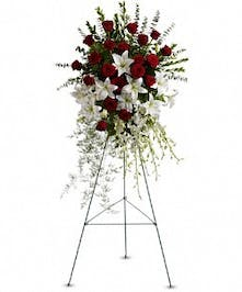 Sympathy spray of red roses and white lilies with greenery presented on an easel.