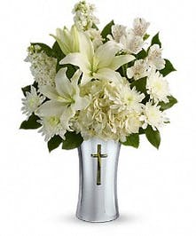 White flowers in a ceramic vase with cross cutout.
