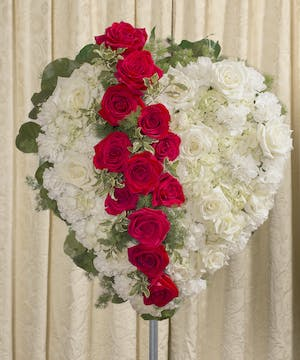 Sympathy heart of white flowers accented with red roses and foliage.