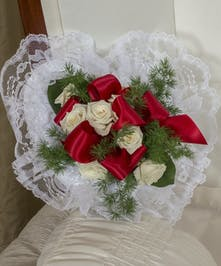 Satin pillow decorated with red and white roses, ribbon and greenery.