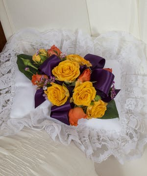 Satin pillow accented with vibrant yellow and orange roses.