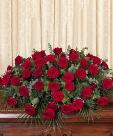 Casket spray of all red roses and greenery.