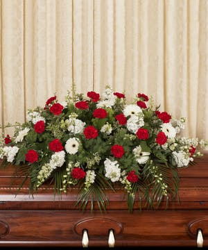 Casket spray of red and white flowers and greenery.