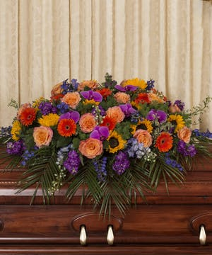 Casket spray of vibrant assorted flowers.