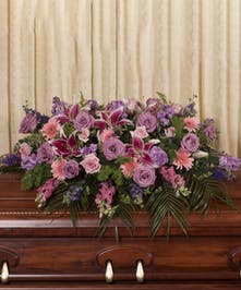 Casket spray of pastel roses, gerbera daisies, lilies and more.