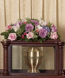 Floral arrangement of pastel roses and orchids to adorn the top of an urn ark.