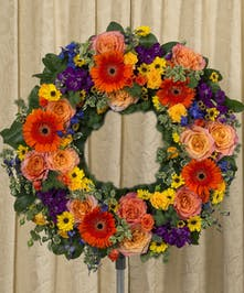 Sympathy wreath of gerbera daisies, roses, stock and more in vibrant colors.