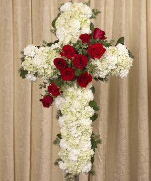 White floral cross white red flower accents and greenery displayed on an easel.