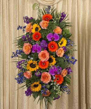 Sympathy spray of gerbera daisies, orchids, roses, sunflowers and more in vibrant colors.