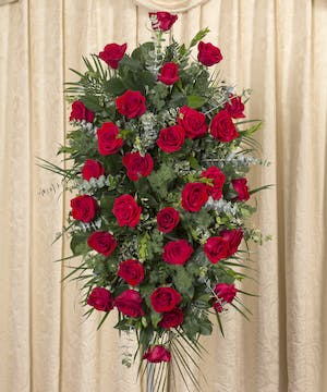 Sympathy spray of all red roses and greenery displayed on an easel.