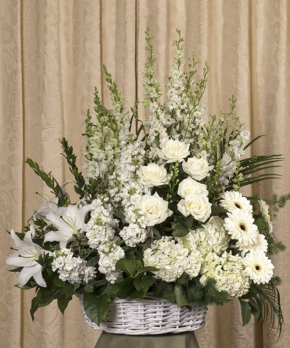 Elegant white wicker basket funeral arrangement kittelberger florist sympathy arrangement of white roses orchids lilies gerbera daisies and more in a izmirmasajfo