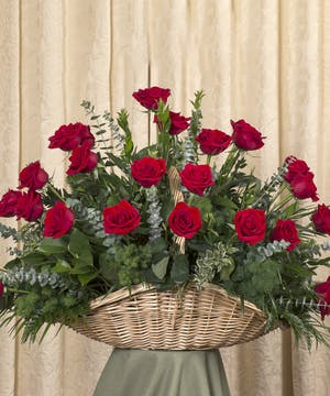 Sympathy basket of red roses and assorted greenery.