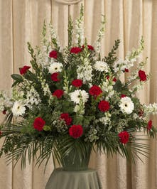 Red and white funeral basket of snapdragons, gerbera daisies, carnations and more.