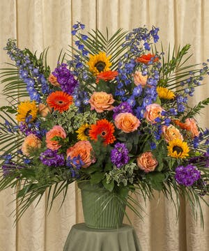 Funeral basket of vibrant assorted flowers.