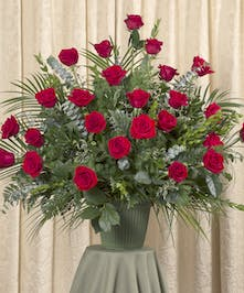 Sympathy arrangement of two dozen red roses and assorted foliage.