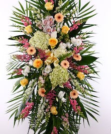 Sympathy spray of peach and yellow flowers with greenery displayed on an easel.