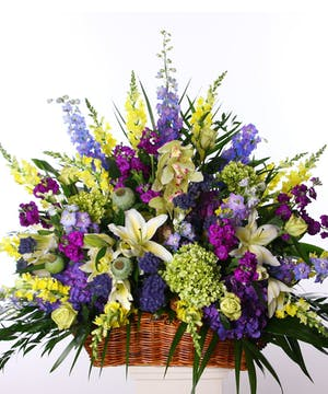 Sympathy basket of purple, green and blue flowers.