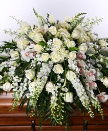 Casket spray of all white flowers including roses, snapdragons and orchids.