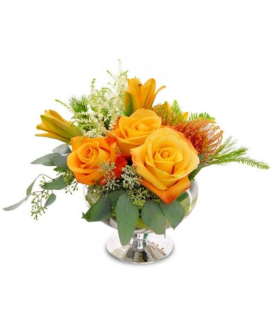 Orange roses, lilies, and protea with greenery in a mercury compote vase.