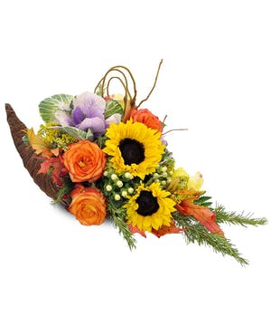 Cornucopia centerpiece filled with sunflowers, roses, hypericum, rosemary and purple kale.