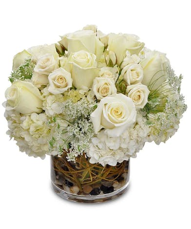 All-white flower bouquet in a clear glass cylinder vase.