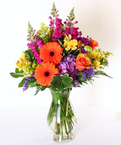 Jewel toned flowers in a clear glass vase.