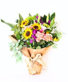 Loose wrapped bouquet of fresh flowers tied with a bow.