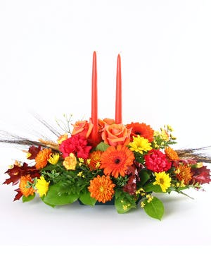 Fall centerpiece of orange roses, daisies, mums, and more accented with oak leaves and two orange taper candles.