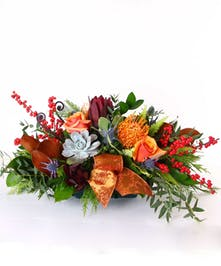 Centerpiece filled with fall flowers and accented with ribbon and succulents.