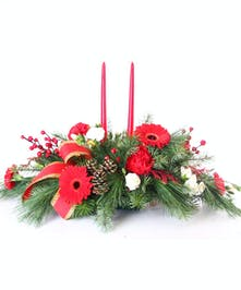 Centerpiece of mixed winter greens, berries, pine cones, and red and white flowers with red taper candles.