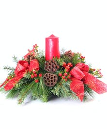 Christmas centerpiece with a red pillar candle, mixed greens, berries and red ribbon.