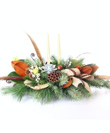 Winter centerpiece of greenery, pine cones, feathers, flowers and more.