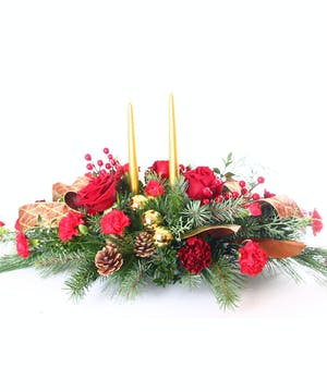 Centerpiece of red flowers and berries with winter greens, pine cones and gold candles.