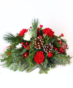 Red and white floral centerpiece with winter greenery, pine cones and berries.