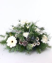 Holiday centerpiece of assorted white flowers, pine cones, and winter greenery.