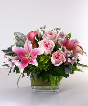 Roses, lilies, calla lilies, stock and assorted greens in a glass cube vase.