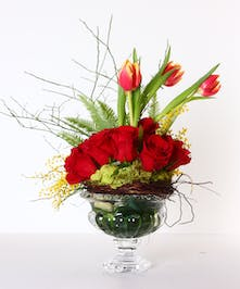 A cluster of red roses arranged in a glass urn with tulips and greenery.