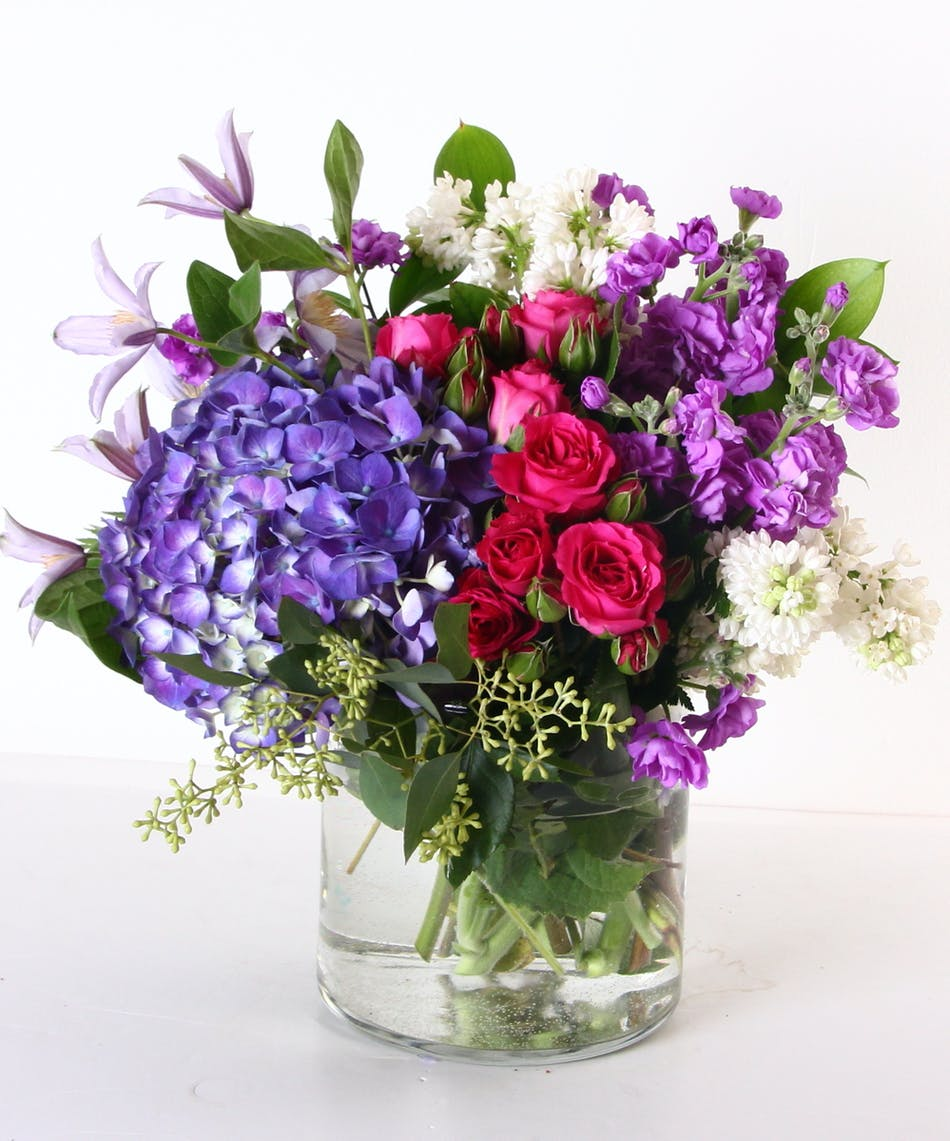 Lilacs, hydragnea, stock and spray roses in a clear glass vase