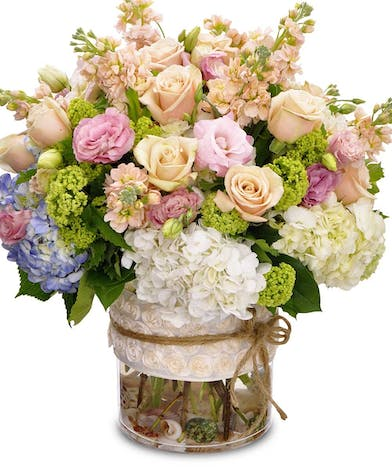 Hydrangea, roses and lisianthus in a cylinder vase.
