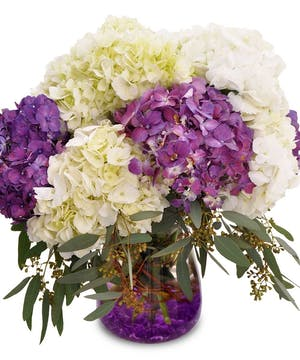 Purple and white hydrangea in a glass cylinder accented with purple gems.